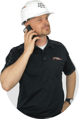 Man in black shirt and hardhat on cell phone
